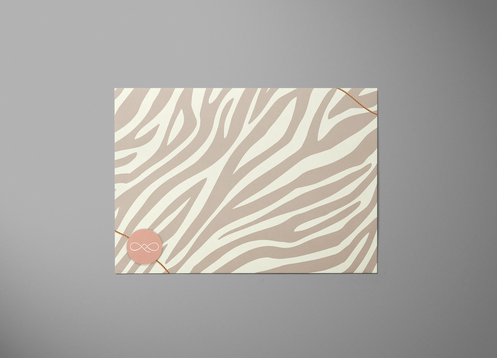 Simple Sexy envelope design in a blended zebra pattern with a touch of gold at opposite corners and logo in lower left.