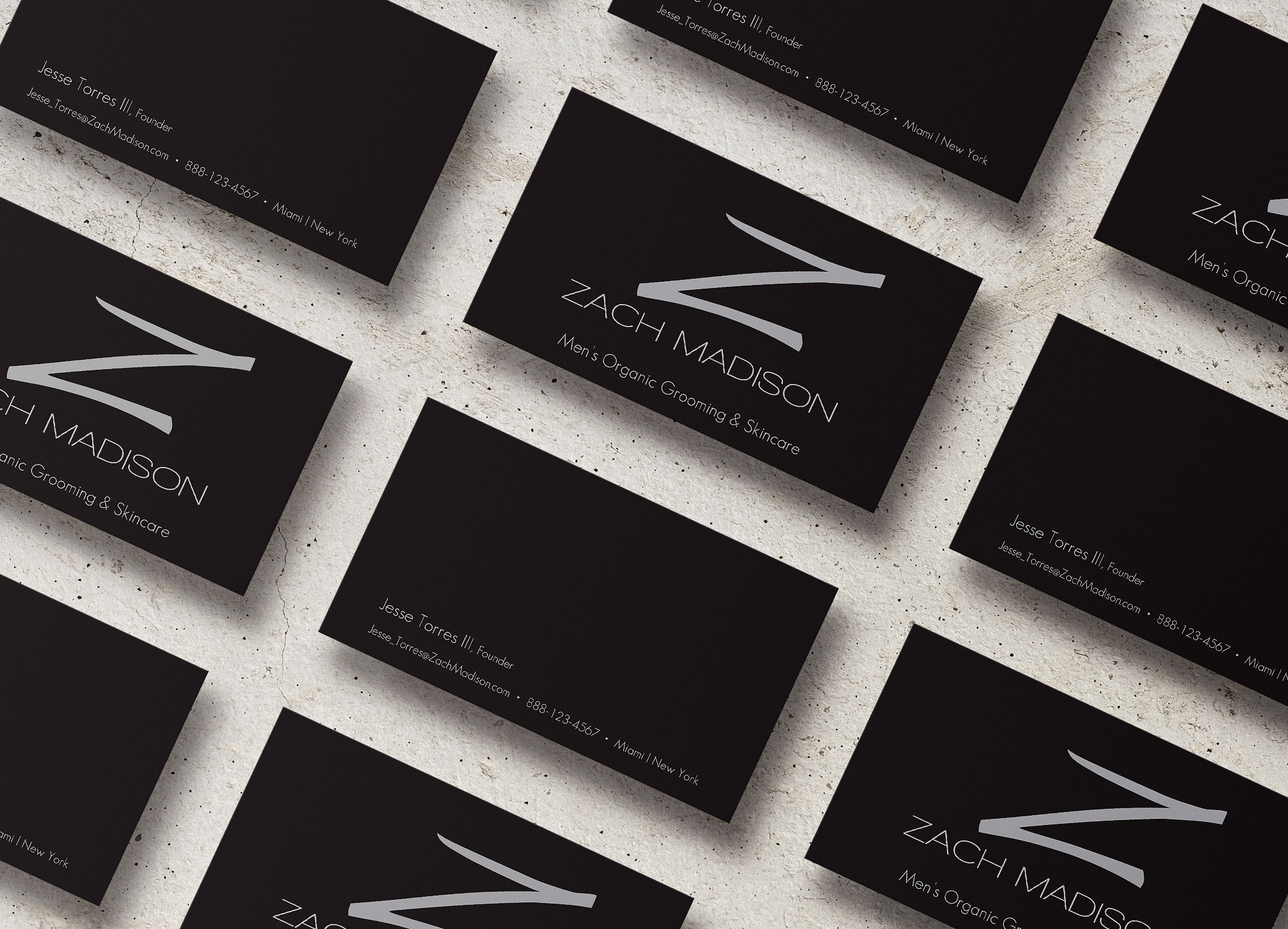 Zach Madison black business cards with metallic 'Z' arranged in slanted rows showing front and back on granite backdrop.