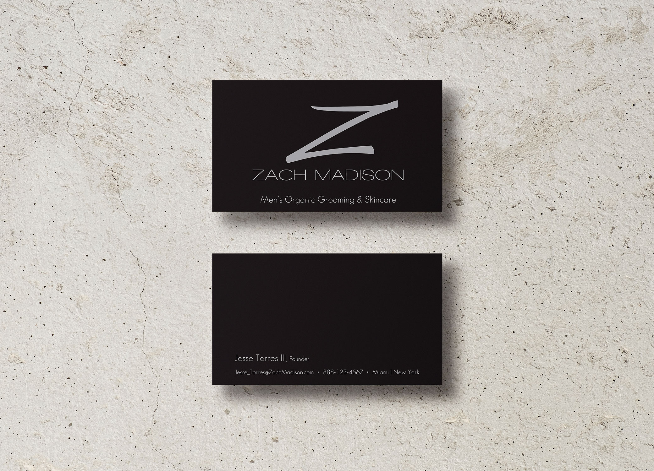 Zach Madison black business cards with metallic 'Z' showing front and back on top of granite backdrop.