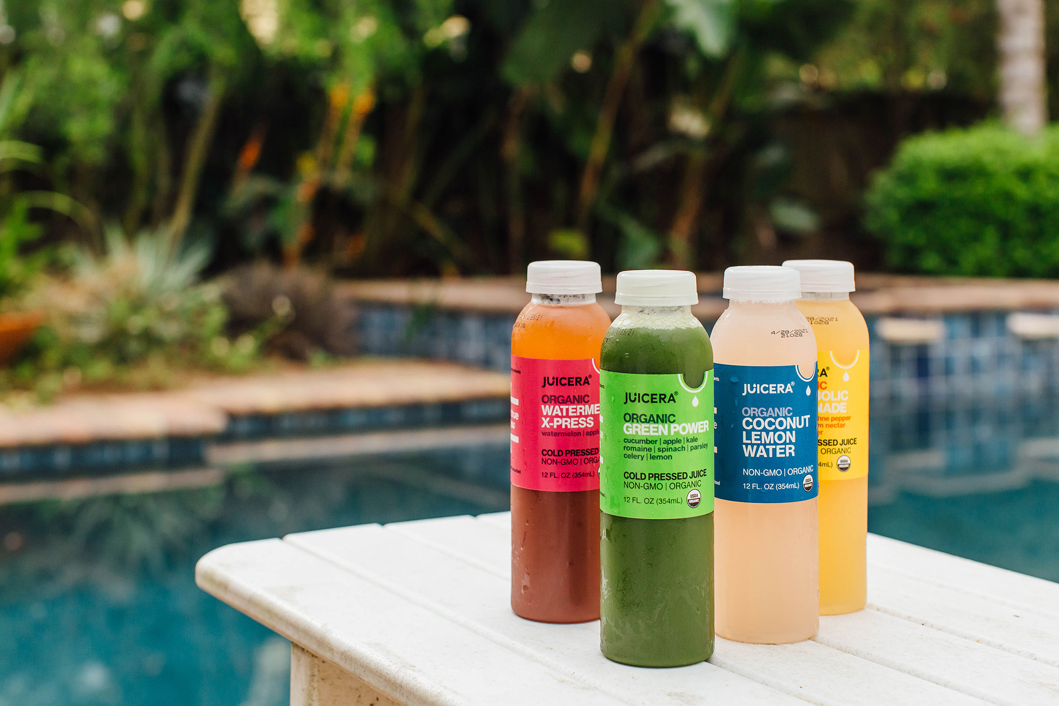Juicera packaging design showcased poolside with different flavors displayed on a table.