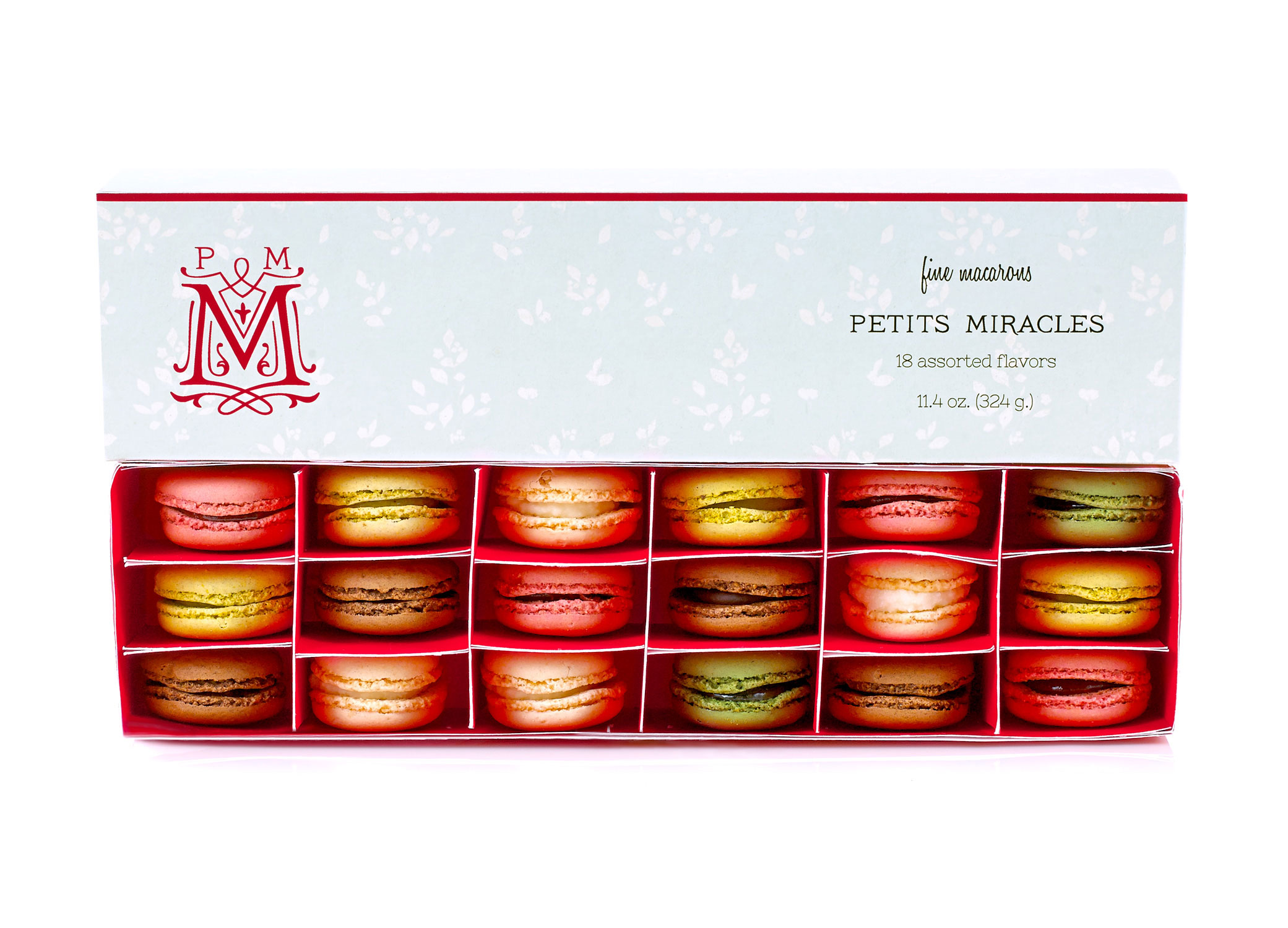 """Petits Miracles packaging design with macaroons in the box and swirls around """"M"""" icon next to type."""