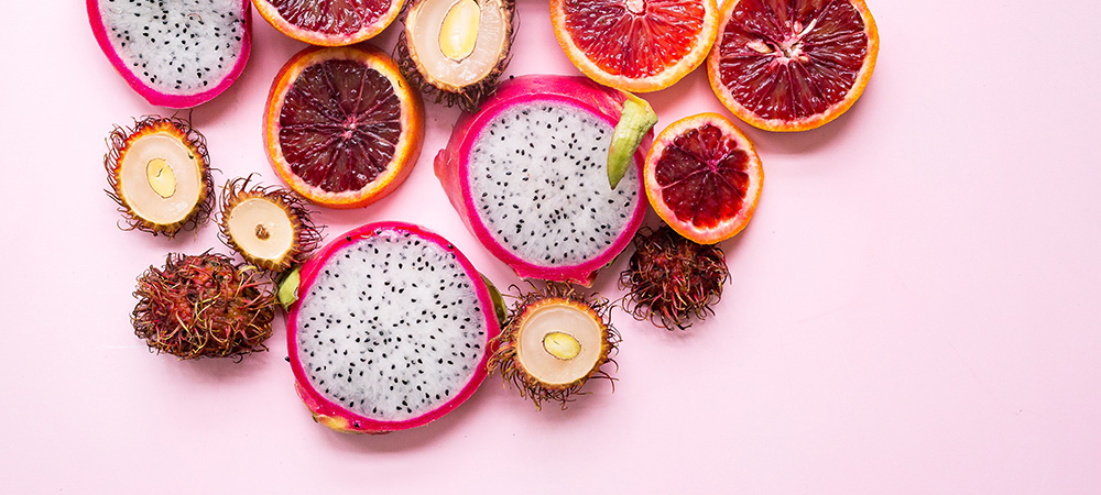 Sliced passion fruit bundle laying on a light pink backdrop.