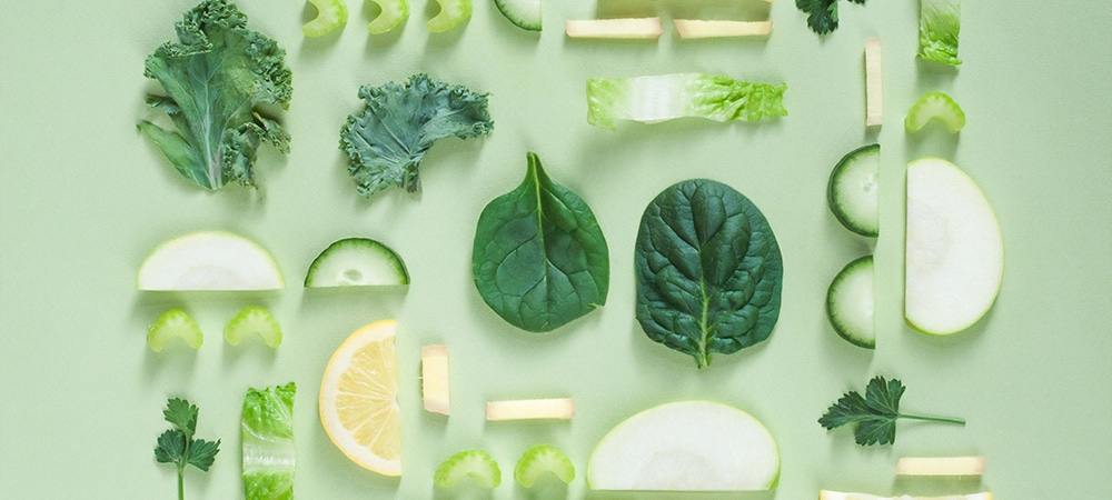 Slices of different types of vegetables and some fruits all ranging in colors of green.