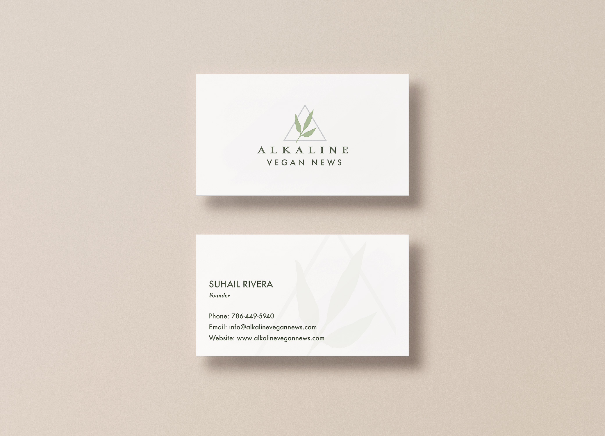Alkaline Vegan News business cards arranged in stacks to show front and back view against a light beige backdrop.