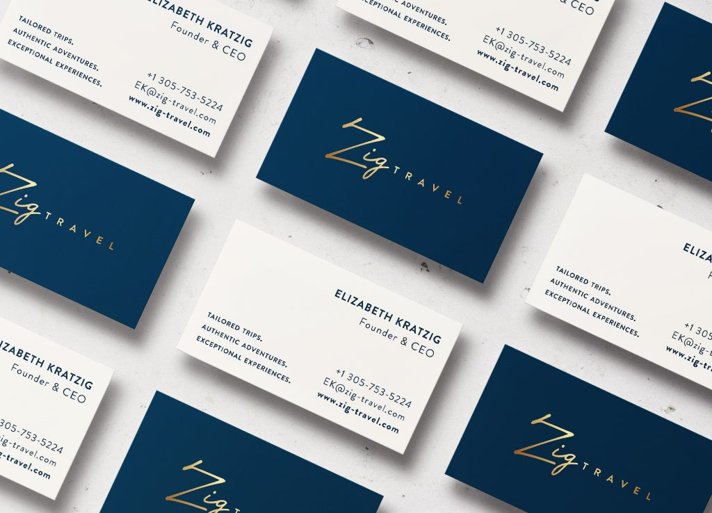 Zig Travel business cards in white and navy with luxe gold lettering arrayed in diagonal rows to show front and back.