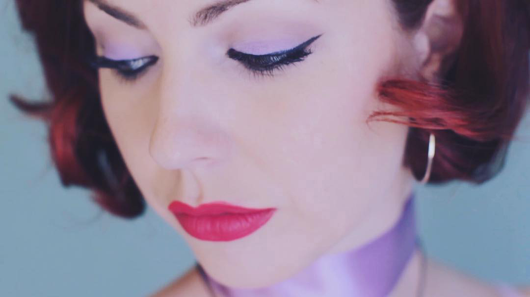42 Dubonnet influencer showcasing featured sultry makeup look with black liner and bright red lipstick.