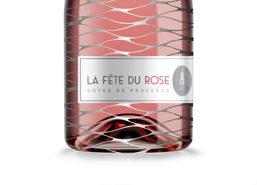 St. Tropez Rose wine bottle packaging design close-up view showing label with St Tropez church steeple against wave-like silver mesh.