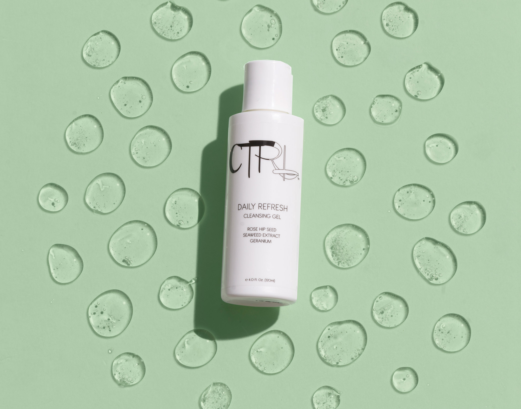 CTRL Cosmetics packaging design showcasing skincare product against light green backdrop with drops of liquid around the bottle.