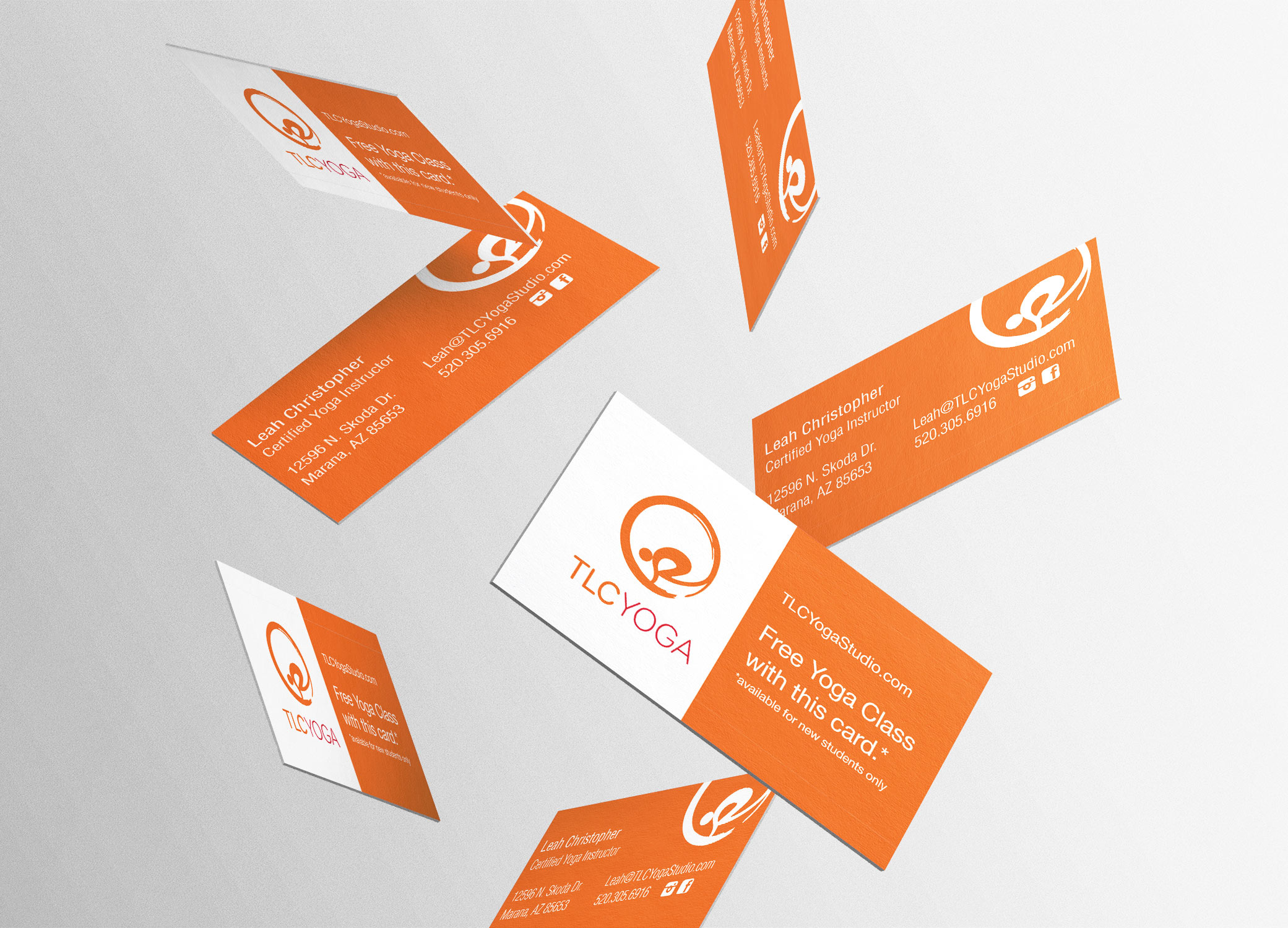 TLC Yoga free-falling business cards in orange and white against a grey background.