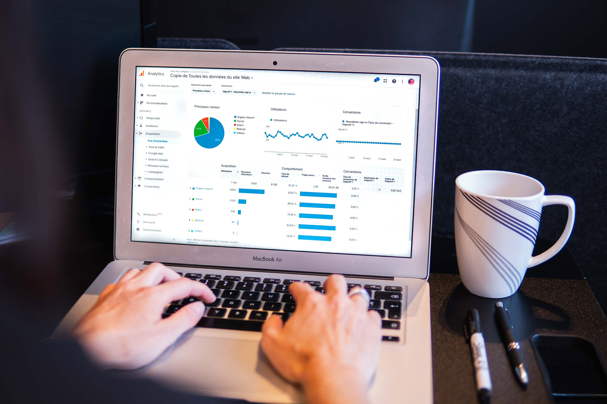 Person tracking their SEO analytics on laptop with analytics on screen.