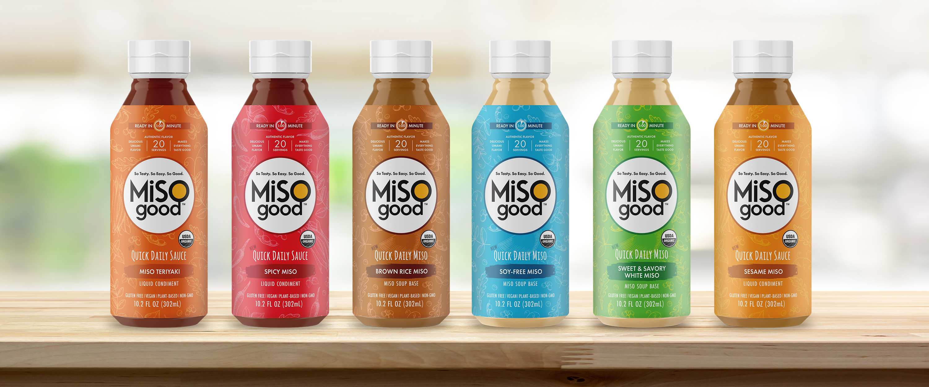 MiSOgood graphic design for food packaging showing a row of bottles in bright colors with white logo and hand drawn graphics on kitchen counter.
